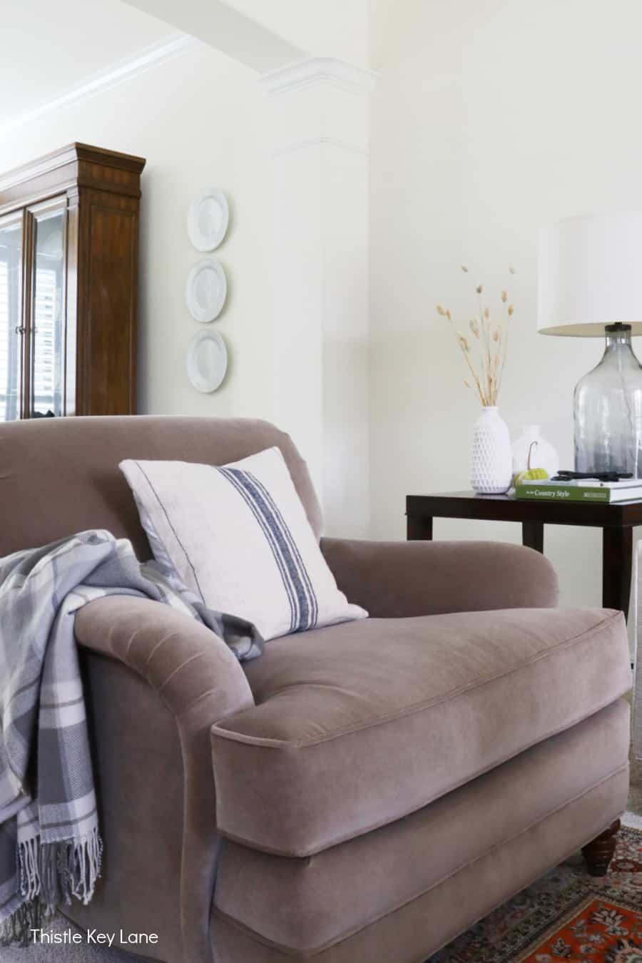 Taupe velvet chair with grain sack pillow and a plaid throw.
