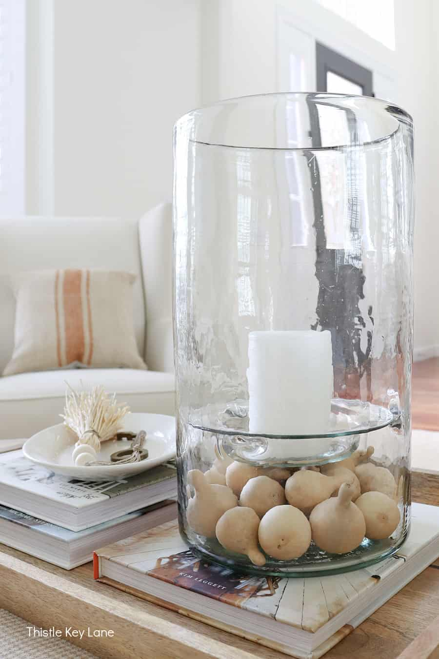 Glass hurricane candle holder with mini gourds. Subtle Ways To Decorate For Fall.