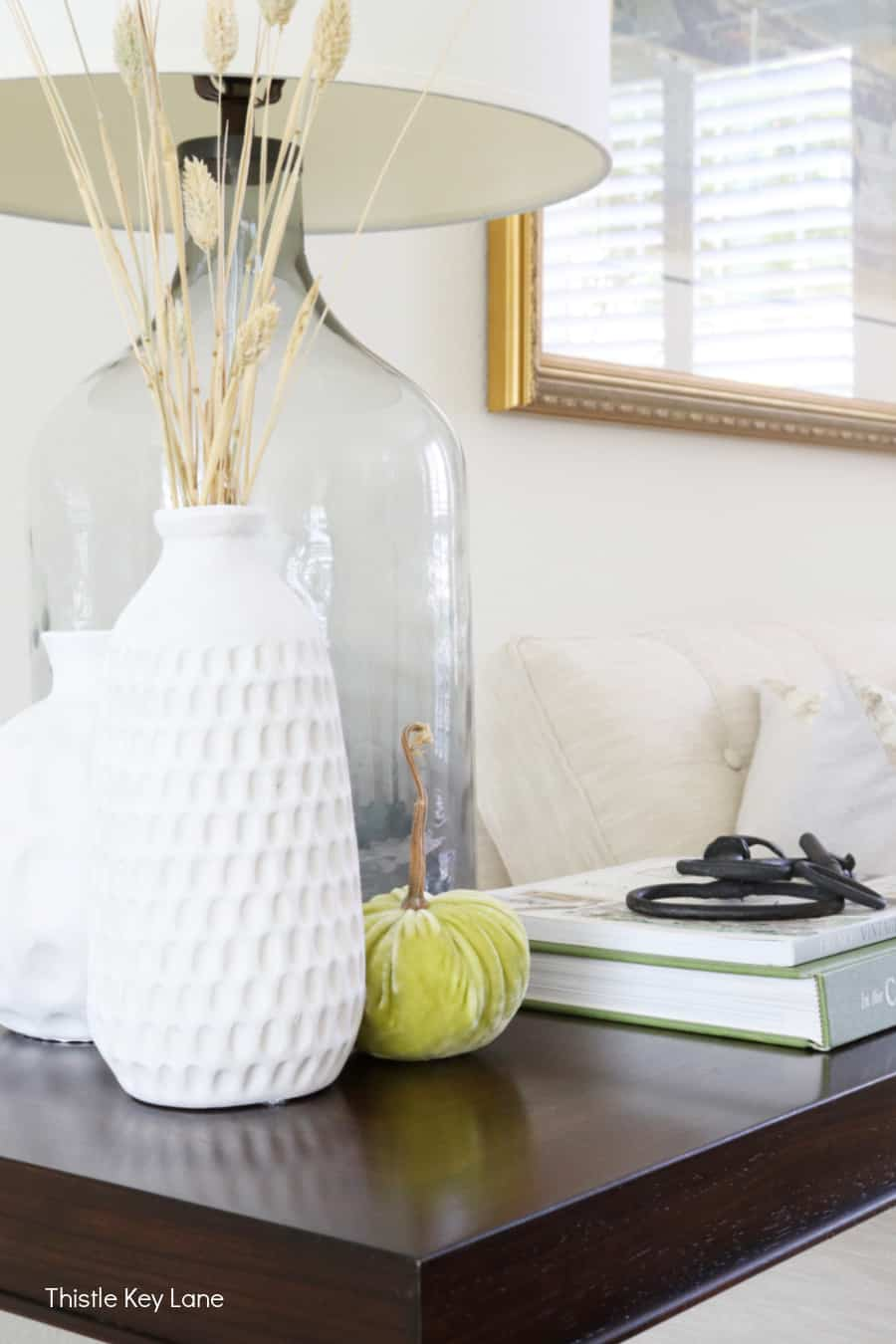 White vases, a green velvet pumpkin, iron keys on top of books. Subtle Ways To Decorate For Fall.