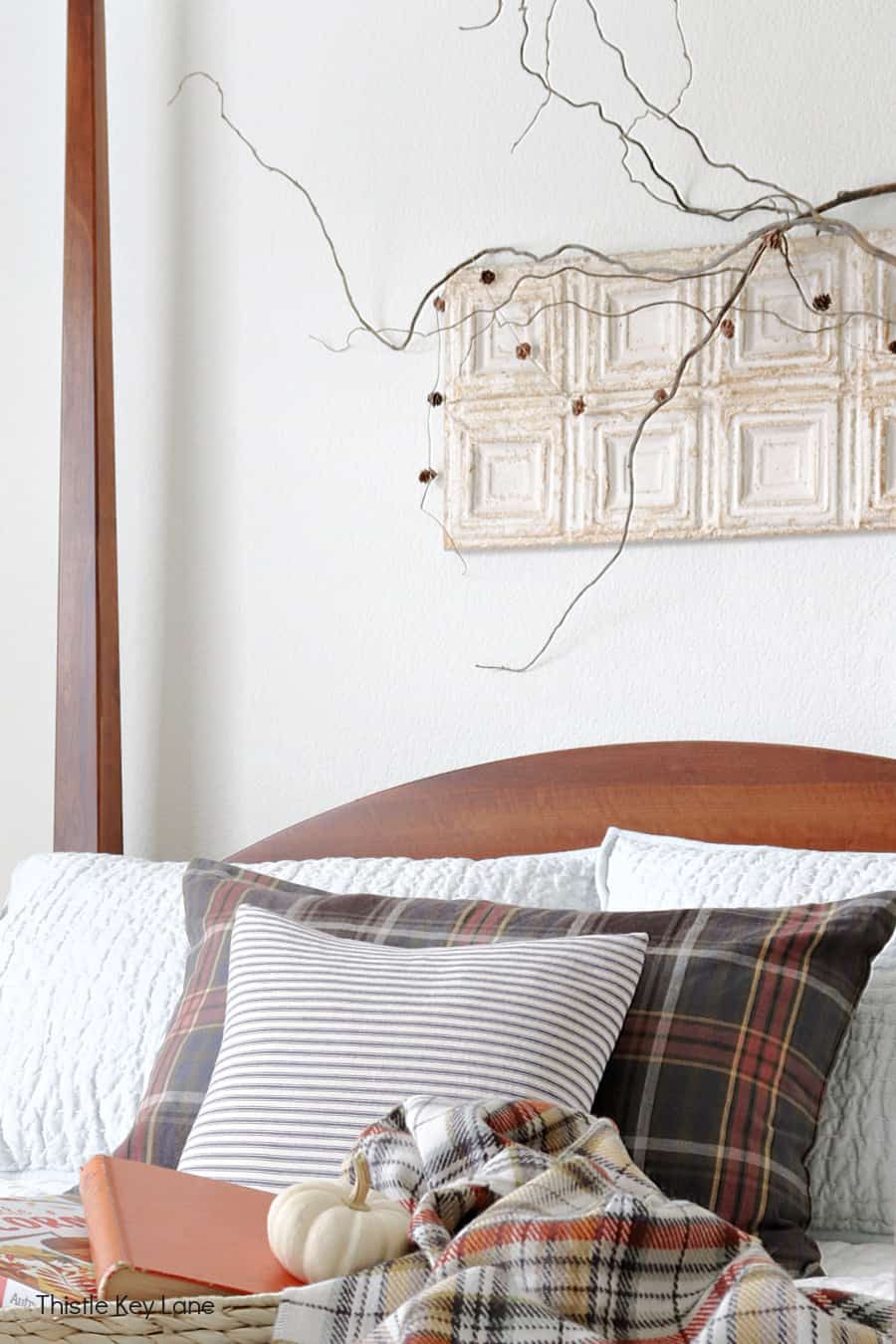 Accent pillows ticking and plaid on a bed. Simple Fall Bedroom Ideas.