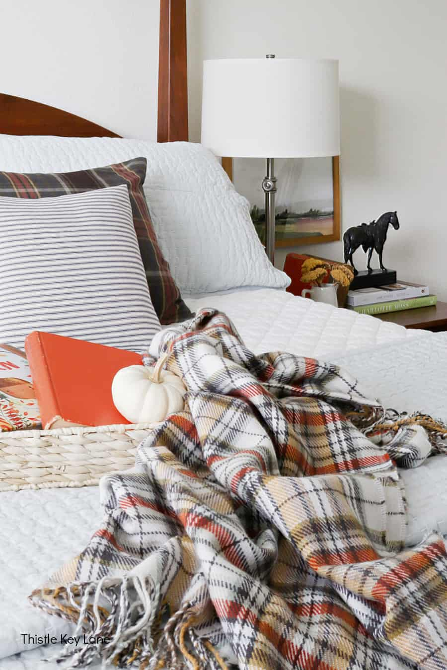Tray with plaid throw on a bed with view of the nightstand. Simple Fall Bedroom Ideas.
