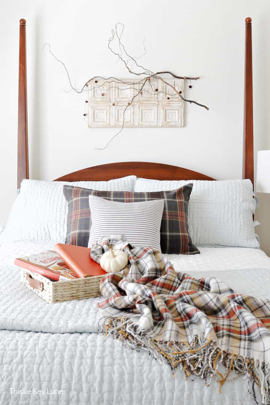 Plaid throw and pillow on bed with white and blue bedding. Simple Fall Bedroom Ideas.