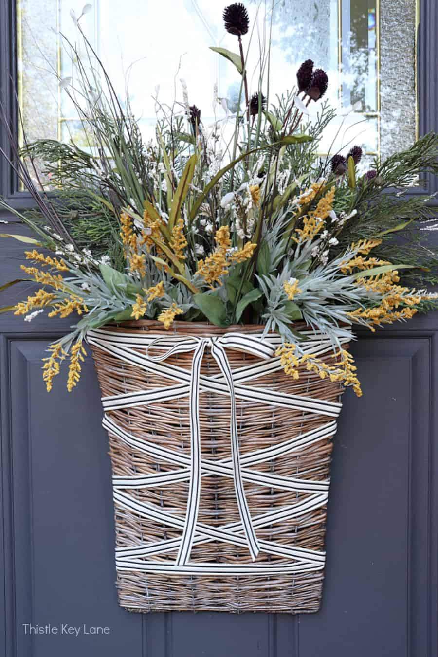 Fall door basket with white ribbon and fall foliage. Simple Fall Porch And Entryway Ideas.