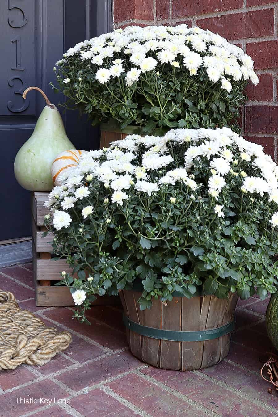 White mums and gourds on a porch. Simple Fall Porch And Entryway Ideas.