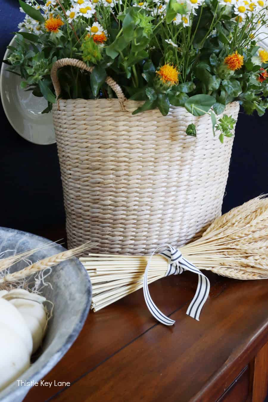 Wheat stalks tied with ribbon and a basket of fall flowers.