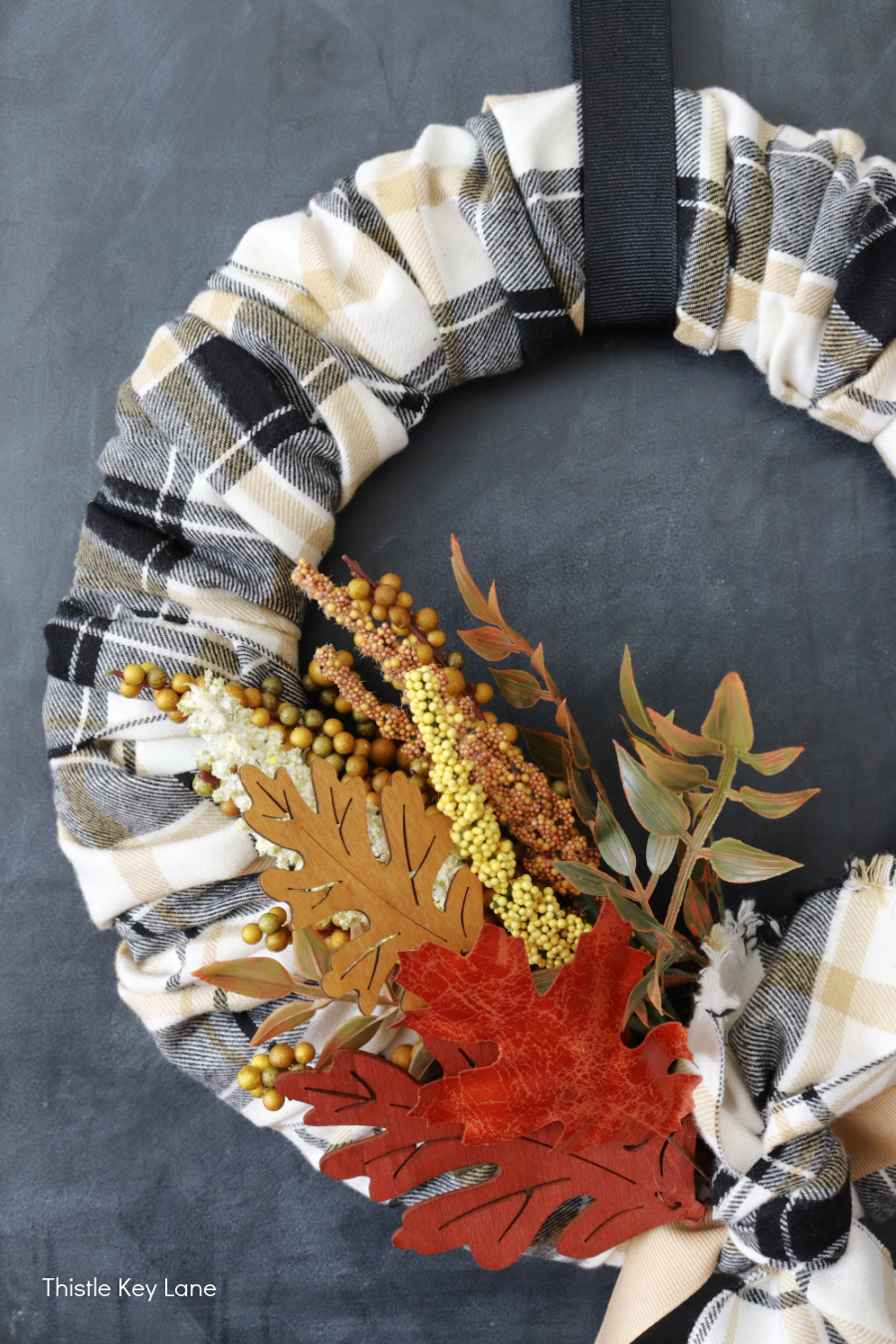 Fall leaves and foliage on a wreath. DIY Plaid Fall Wreath With Autumn Colors.