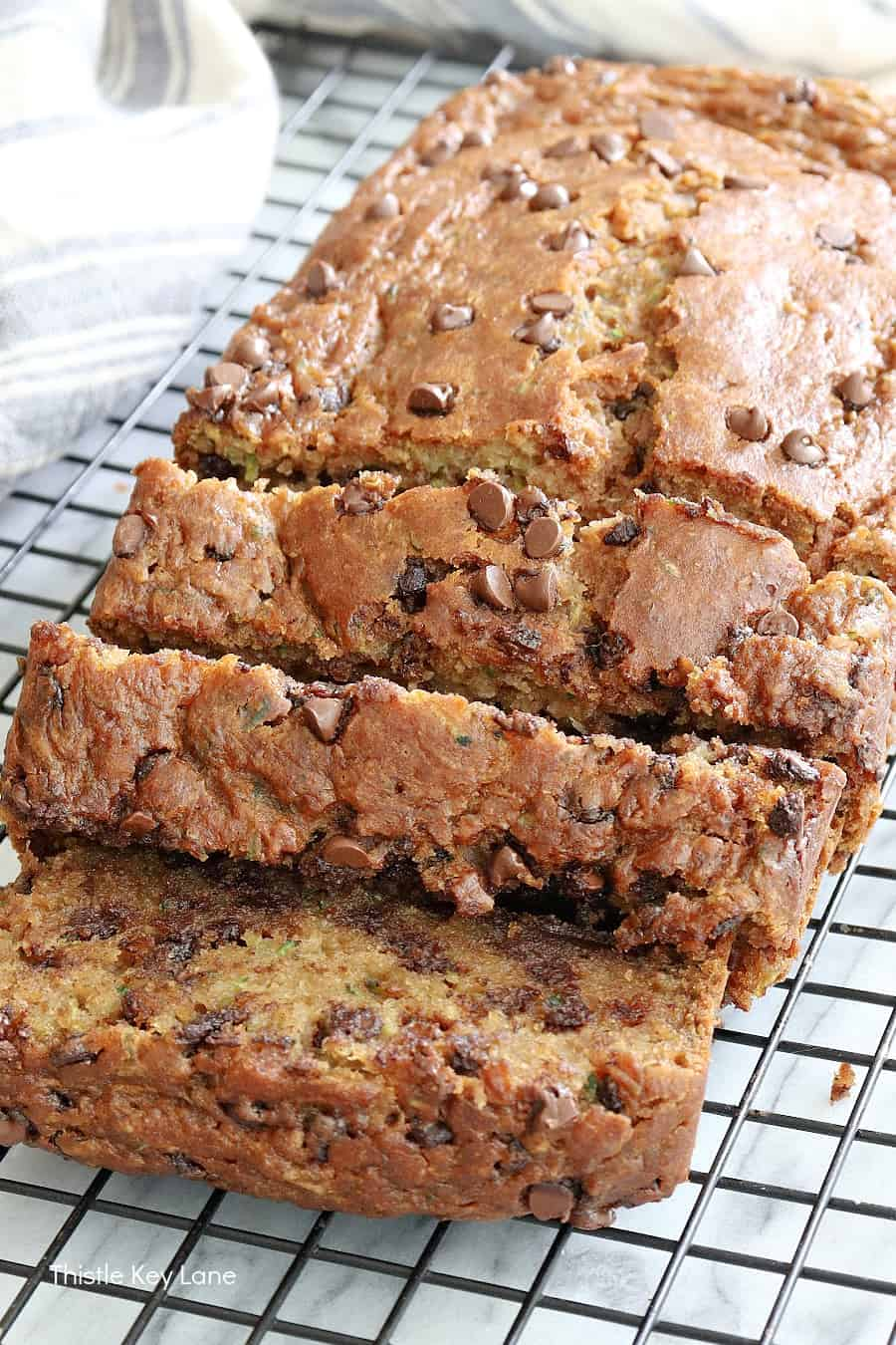 Zucchini bread sliced on a cooling rack.