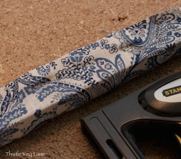 Staple fabric to particle board stretching from side to side then end to end.