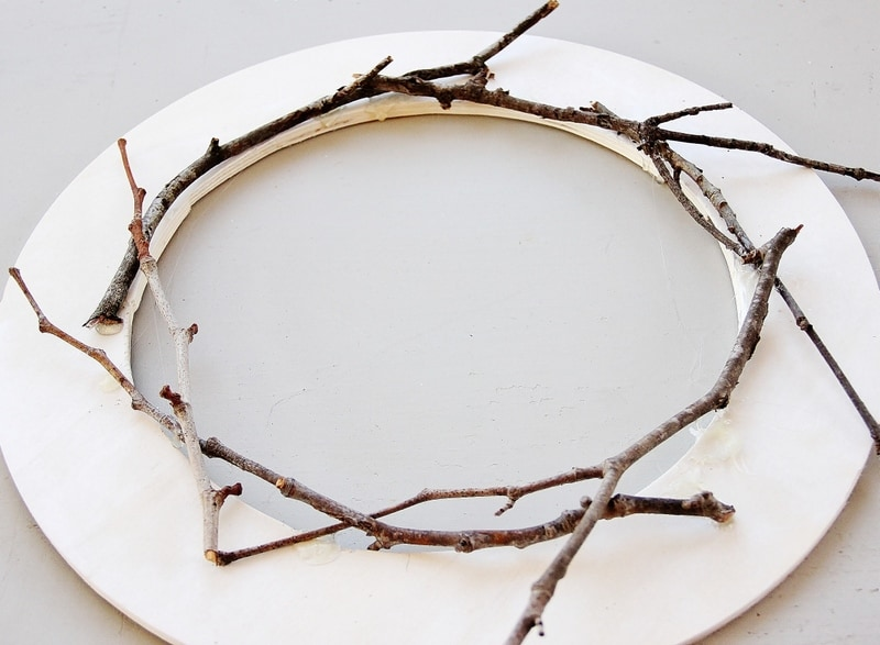 Add your first layer of branches to the spray painted wooden circle to start your white twig wreath.