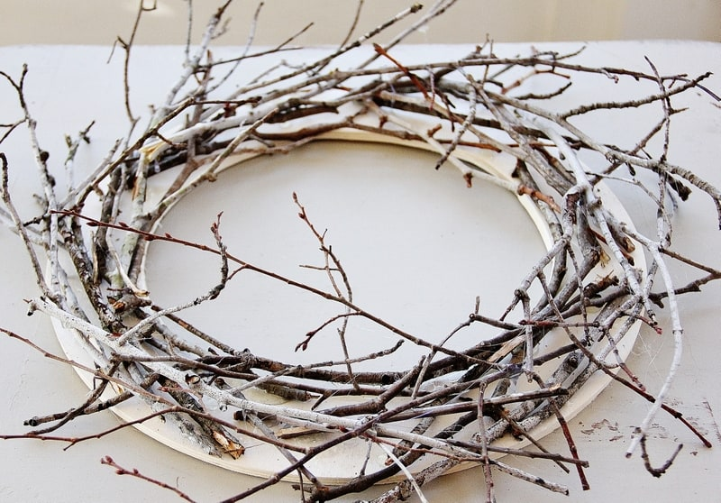Continue to add branches and hot glue each stick in a clock-wise pattern.