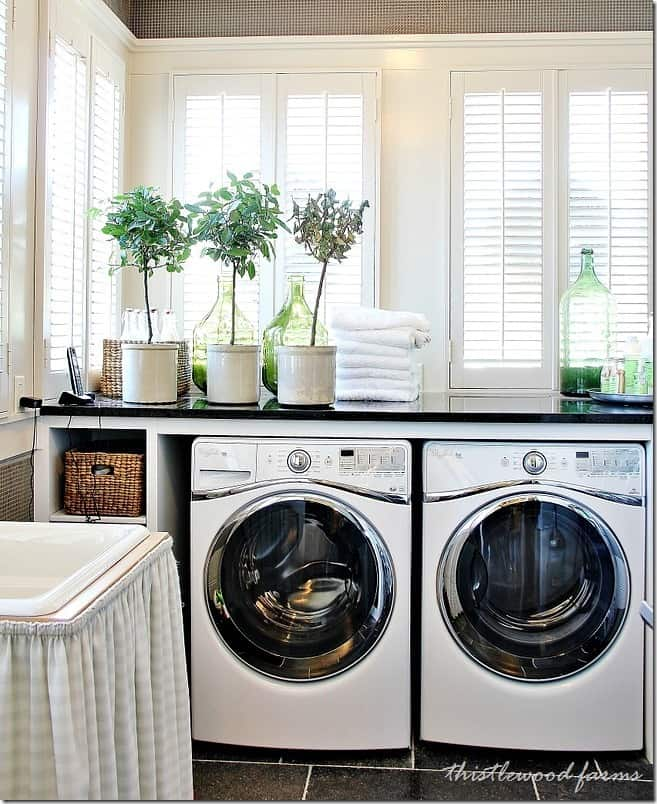 This functional laundry room has a custom build marble counter with drawers and functional storage