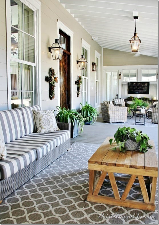 This front porch is a collection of patterns and textures, completed with a rustic barn wood coffee table