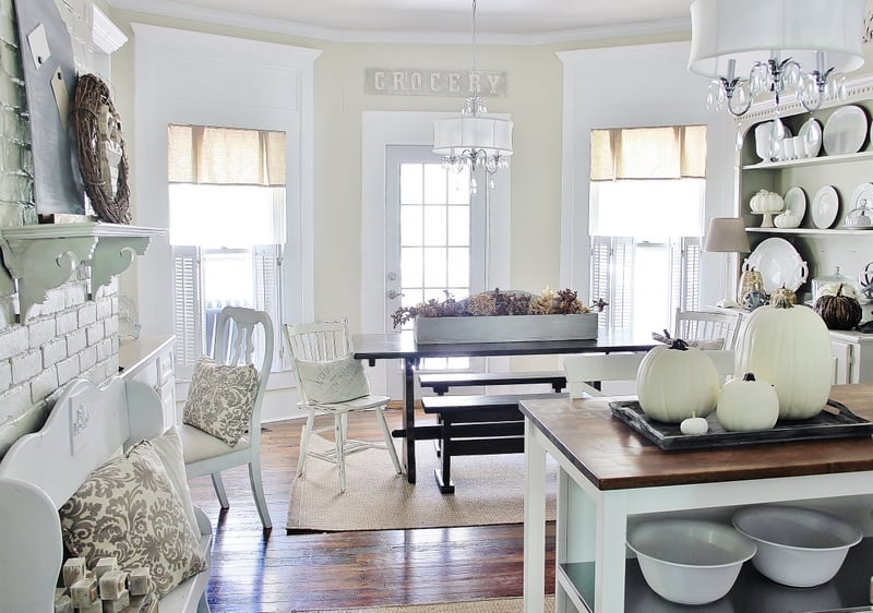 An all white and light cream kitchen seen; on the counter is a metal tray with white pumpkins