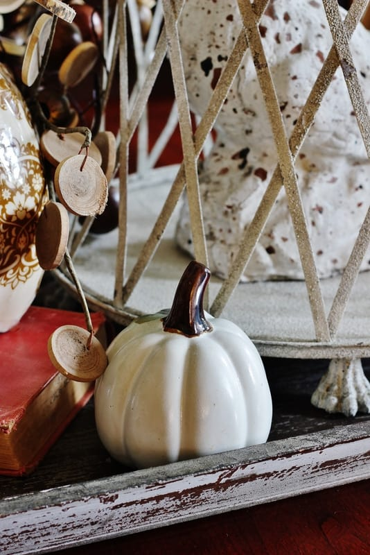 A white porcelain pumpkin sitting on a wooden tray
