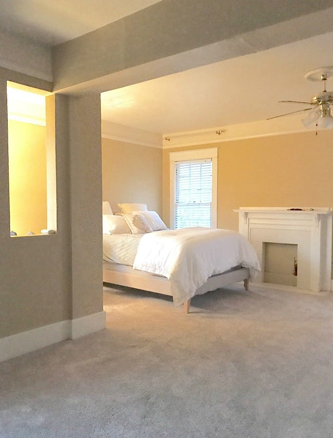 A neutral colored bedroom with soft lighting and gray and brown walls