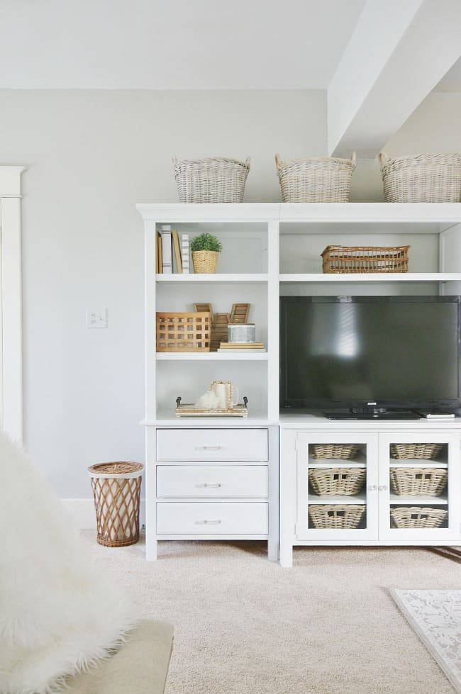 This farmhouse bedroom is complete with an entertainment center and bookshelf decorated with woven baskets and books