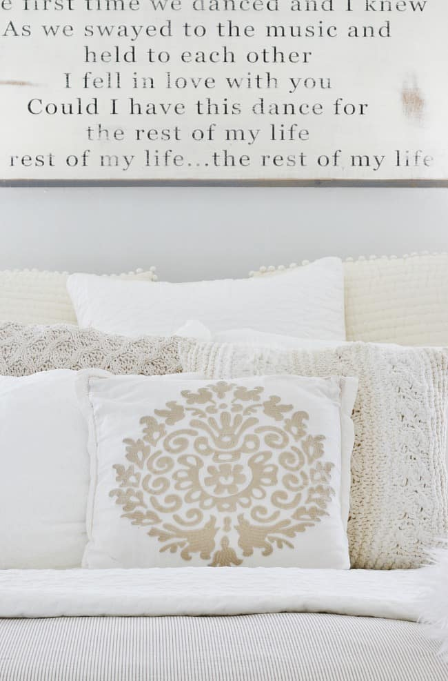 Soft linen pillows with gray and neutral fabric colors, and a decorative wood sign on the wall