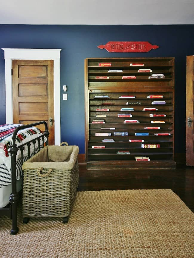 The bookcase against the navy wall with multicolored books