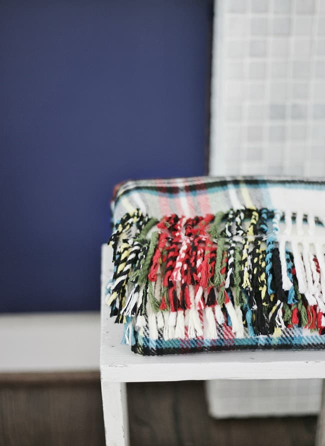 The beautiful Indigo blue wall in the background compliments the red, green, and yellows in this woven throw blanket