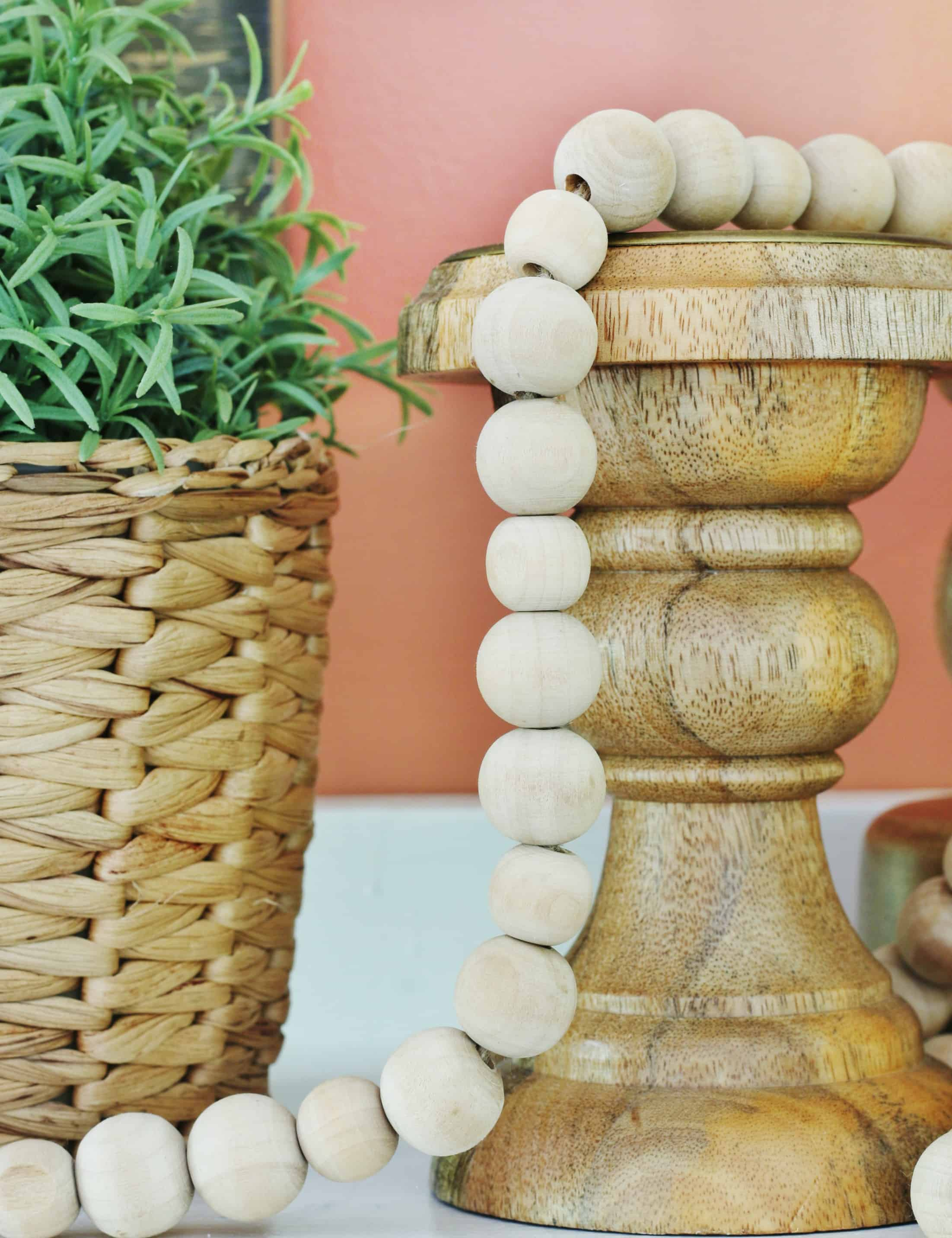 Mantle decorations of a trio of wood candlesticks, wood beads and a small potted plant in a basket