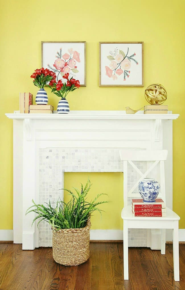 A bright, vibrant yellow wall - paint color is  Overjoy SW 6689. The mantle is decorated with blue and white striped vases filled with red flowers and framed pastel floral paintings