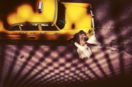 At this 2012 Lighthouse at Chelsea Piers wedding the bride and groom rented a vintage New York taxi to take them around the city for their portraits. They requested some pictures with this cab, and I was only too happy to oblige. Whenever I have a request to take a photograph of the bride and groom in front of an item, vehicle, or building I try to approach it in a slightly new and different way. We had been at the High Line taking photographs of the bride and groom together, and were getting ready to head back over to the Lighthouse for their ceremony. The cab was waiting for us down at the curb. When I looked down on the cab from the High Line staircase, I knew I had an opportunity to make a creative photograph of the scene before me. I placed the bride and groom next to the front of the cab, and I climbed the stairs back up onto the High Line. This image was shot through the metal fence of the High Line. I love it that the pattern of the dots lead your eye directly to the bride, groom, and cab. I was thrilled to be able to give the bride and groom something other than your standard picture of them just standing in front of the car.