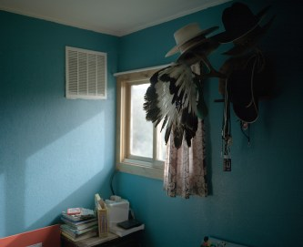 "A war bonnett hangs in the home of Kenneth ""Tuffy"" Helgesson underneath his collection of cowboy hats, in Lodgepole. Helgesson is an important member of the Assiniboine community; he is one of the few remaining natives who is fully fluent in their language, and is a strong advocate for the continuation of traditional culture. Because of his skills and belief in the importance of maintaining culture, Helgesson is a teacher at the local public high school, where he teaches language and culture classes to future generations."