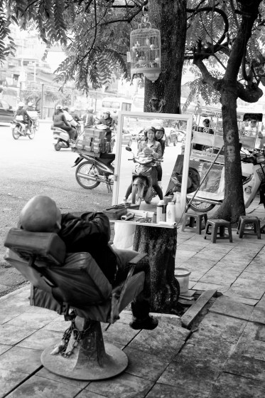 street-barber-asleep-with-girls-on-scooter-in-mirror-in-black-and-white-hanoi-vietnam-copyright-2015-ralph-velasco