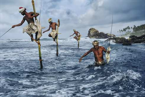 "CAPTION©Masters of Photogra©Masters of Photography: Fishermen at Weligama. Sri Lanka, 1995.MAX PRINT SIZE: 60X80SRILANKA-10006IG: I took this image of men fishing in Weligama off the South coast of Sri Lanka.10/06/2016IG OLD: This is one of the images currently featured in my exhibition at Patricia Conde Galería (@patriciacondegaleria) in Mexico. The exhibition runs until September 3rd, I hope you can visit if you're in the area.I took this image of men fishing in Weligama off the South coast of Sri Lanka.08/13/2015""Fishermen along the southern coast of Sri Lanka cast their lines in the traditional way atop poles so they can work in shallow water without disturbing the fish."" - George Eastman HouseLike outlandish herons, a flock of men clad in traditional saram fish the south coast from wooden perchs. Not long ago their island nation was poised to join Asia's economic dragons, but 13 years of strife have cramped development and kept many Sri Lankans working the land and sea like their ancestors. Vol. 191 No. 101/1997 National Geographic Magazine. Vol. 191, No. 1, pgs. 110-111, January 1997, Sri Lanka: A Continuing Ethnic War Tarnishes the Pearl of the Indian Ocean.NN11429210, MCS1995006K10006book_Iconicfinal print_MACROfinal print_Sao Paulo final print_Birminghamfinal print_HERMITAGEfinal print_Zurichfinal print_Ankarafinal print_UticaFine Art Printretouched_Sonny Fabbri 3/4/2015"