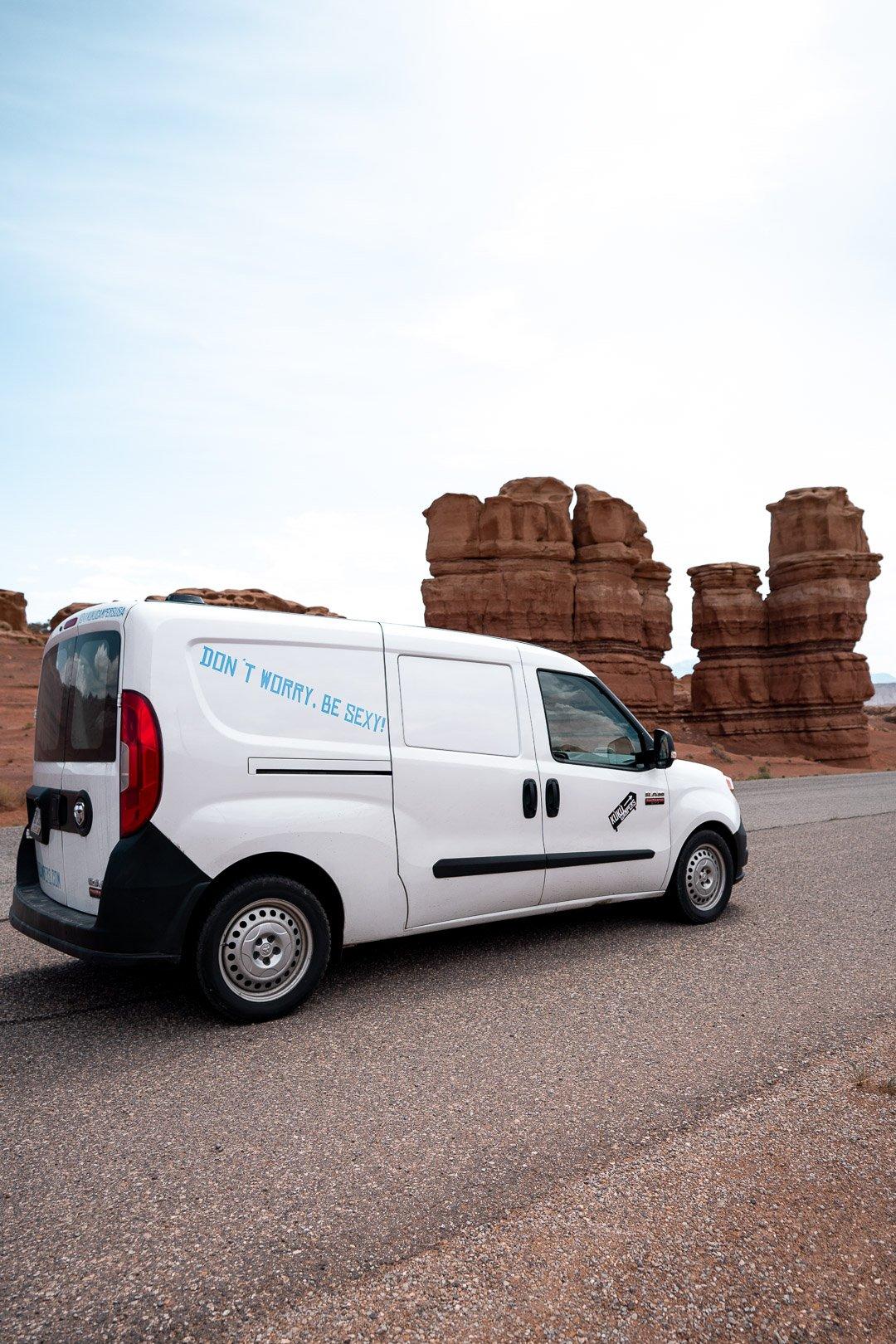 A camper van in front of rock formations in Capitol Reef, Utah