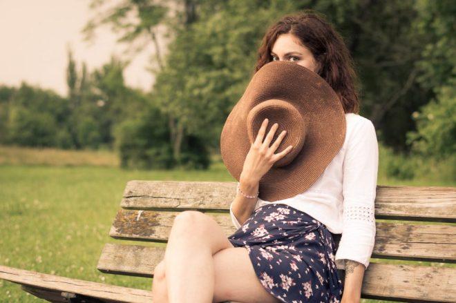 Jeune femme en jupe cachée derrière son chapeau