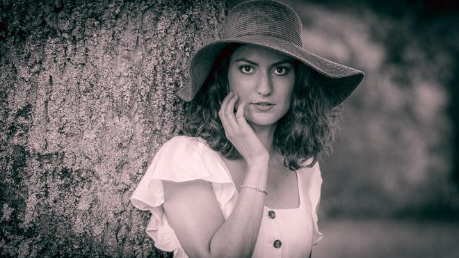Jeune femme en noir et blanc avec chapeau, prenant la pose lors d'un shooting.