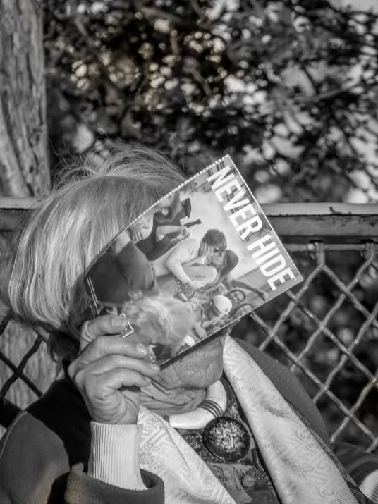 """Photo prise à Paris sur les bords du Sacré Cœur. La vieille dame c'est cachée le visage avec son magasine pour se protéger du soleil laissant apparaitre la publicité qui a comme slogan """"jamais caché""""."""