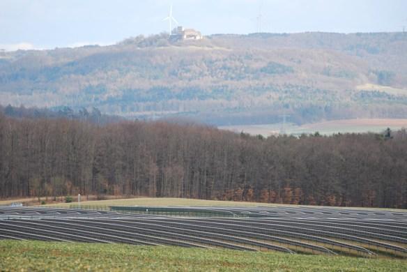 Blick auf die Giechburg aus Westen. Im Vordergrund Freiflächen-Photovoltaikanlage, hinter der Burg Windräder des 200m-Typs in knapp 3 km Entfernung.