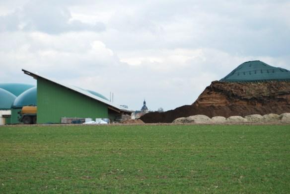 Biogasanlage in Mittelfranken mit Durchblick auf die Dorfkirche.