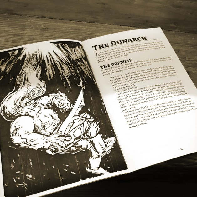 Booklet is opened to a page that has a picture of a person falling shirtless with a sword in a splotchy ink art style. The opposite page has the rules for The Dunarch player.