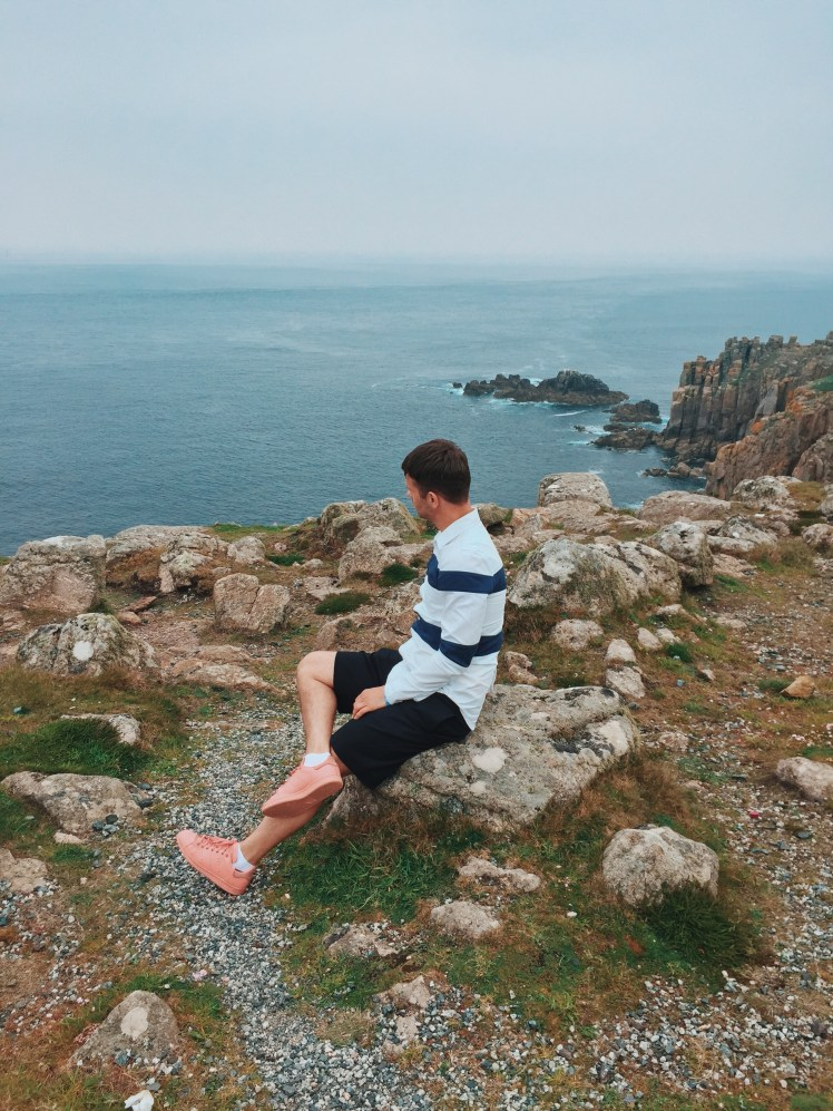 Jacob sitting very relaxed checking out the views of the Atlantic and Celtic sea below. The cliff faces have the waves crashing against them below.