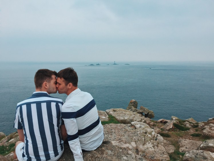 Jacob and Tommy sharing a kiss whilst perched on the rocks against the cliff face and ocean views in the background. The Longships Lighthouse are perfectly visible from where we are situated on the edge of Land's End.