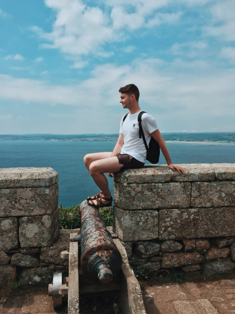 Tommy sitting on the wall next to the cannon pointing towards Newlyn, Cornwall. The view is from the top of St. Michael's Mount giving a vast panoramic stretch of ocean and coastal front.