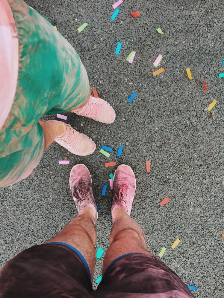 A shot of our trainers which got ruined by the paint and foam as we ran the course. Around our feet are multicoloured confetti pieces.