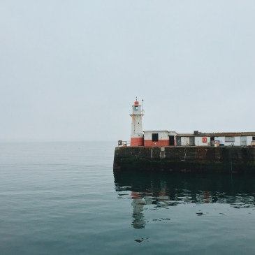 Newlyn harbour lighthouse against a slightly misty ocean