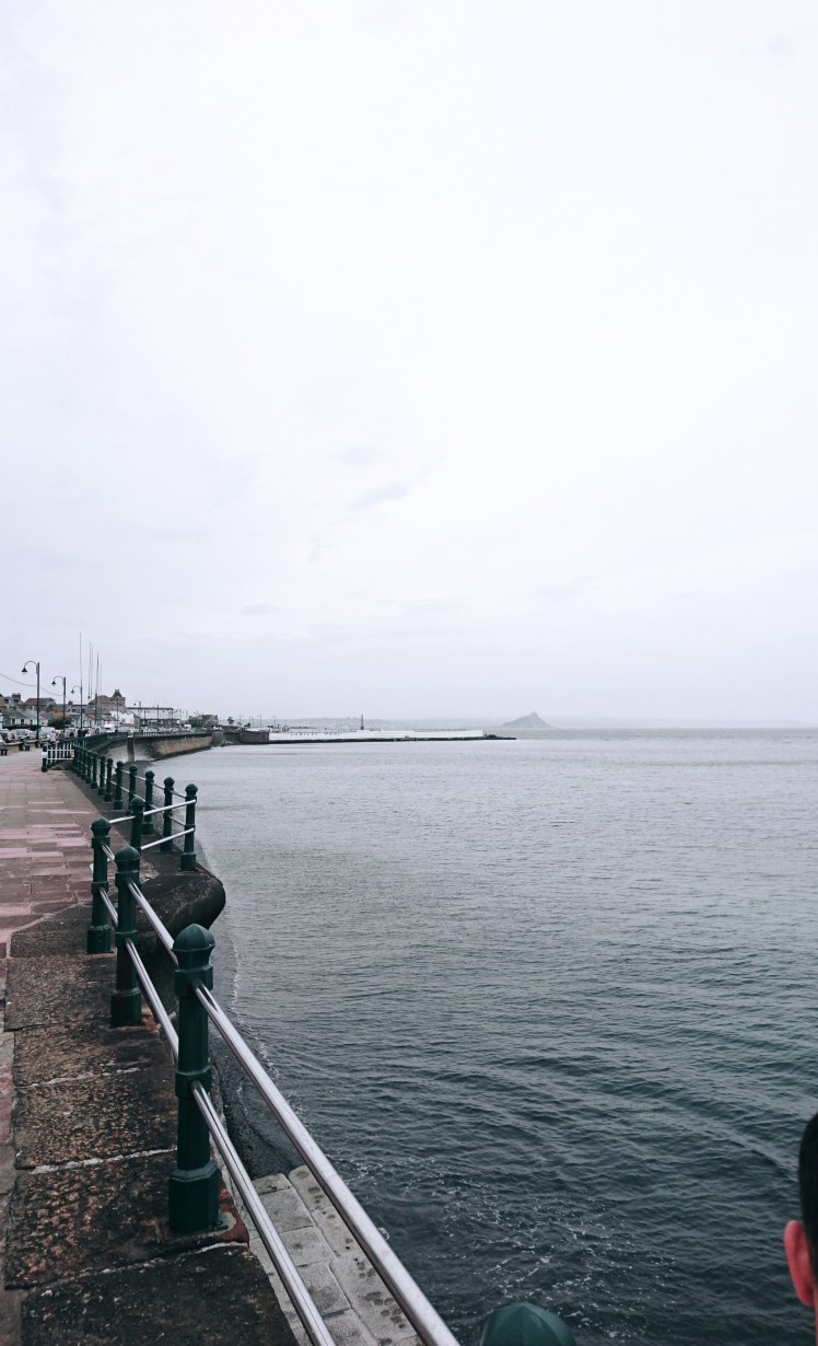 Gloomy weather Penzance beachfront with views of Jubille Pool and St Michael's Mount in the distance