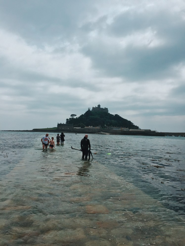 View of the causeway against the St. Michael's Mount during high-tide. The ocean covers the clear path as people in the shot wade through to the mainland.