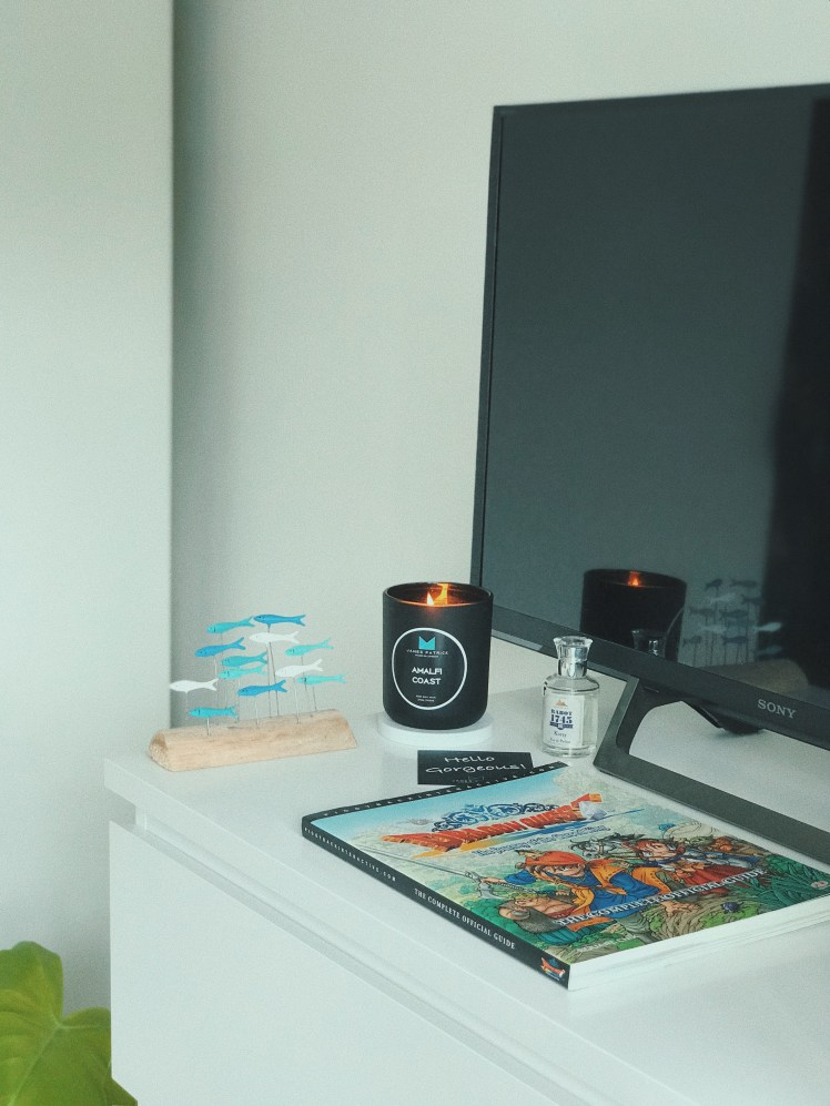 James Patrick Amalfi Coast candle sitting on chest of drawers alongside a little fish sculpture and Rabot 1745 eau de parfum. It is lit and flickering is reflected from the television screen behind. There is also the personal note 'Hello Gorgeous' on the side and the video game guide placed atop too. The game guide reads Dragon Quest VIII [8]