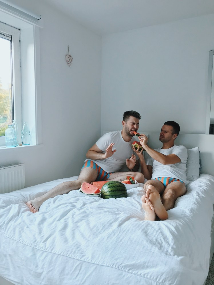 Jacob and myself wearing Shinesty's Orange & Teal Striped, Ball Hammock boxer shorts. The print is thick and loud and quite bold. We are relaxing on top of the bed, whilst eating giant watermelon slices.