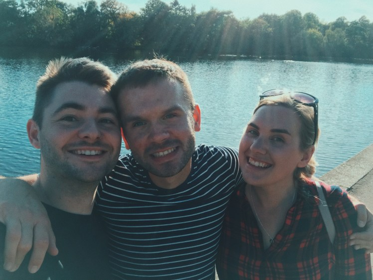 A selfie of Jacob, Meg and myself against a pond close to our home that is glistening in the sunshine.