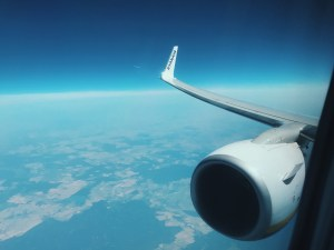 A shot from the planes window looking down at the land and sea below. The edge of the horizon bends with the shape of the globe