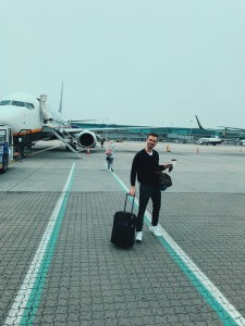 Jacob standing against the planes near the terminals