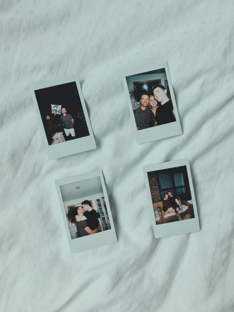 Shot of 4 Instax pictures on the bed. Each one with a cute moment from the day, Meg, Jacob and myself had.