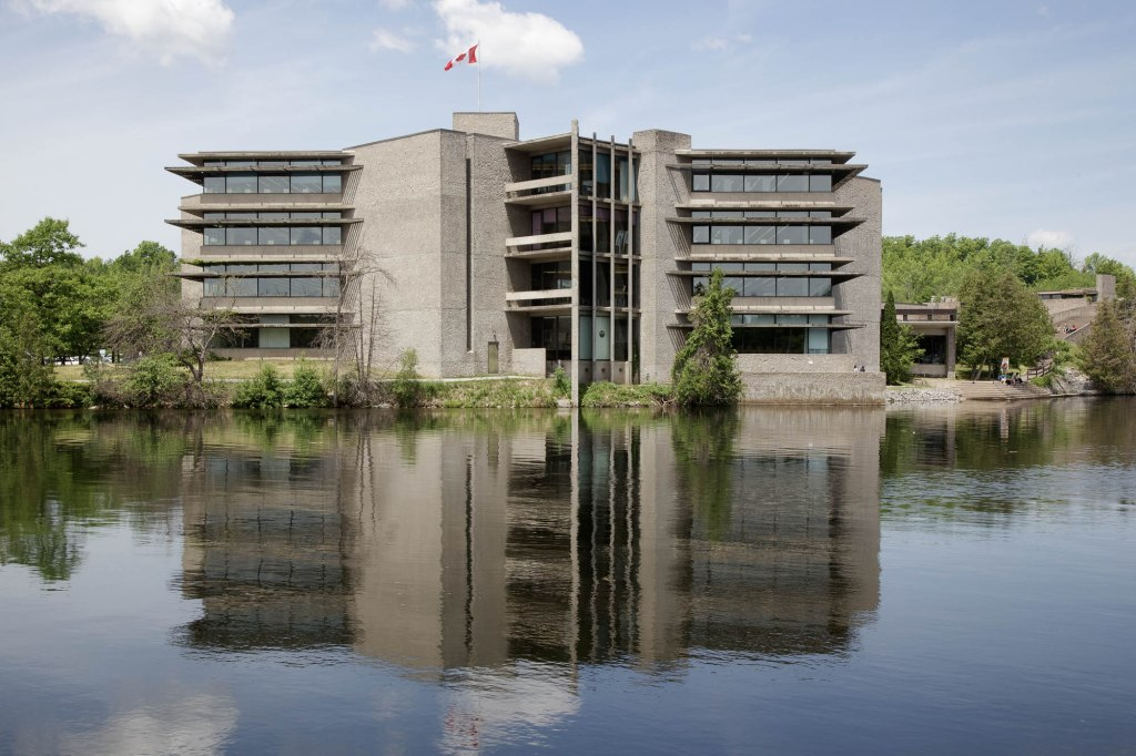 Image of the Bata Library, a brutalist building reflected in a river.